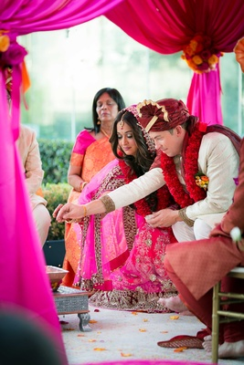 Bride in lehenga and groom in sherwani at outdoor Indian wedding ceremony with pink and red canopy
