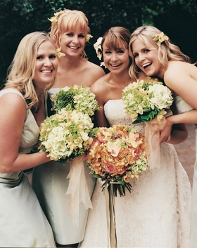 Bridesmaids in short mismatched dresses with green bouquets