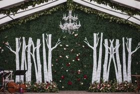 wedding ceremony altar chandelier greenery hedge wall birch tree trunks flowers at base tent