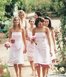 Bridesmaids in pink dresses walk through rose garden