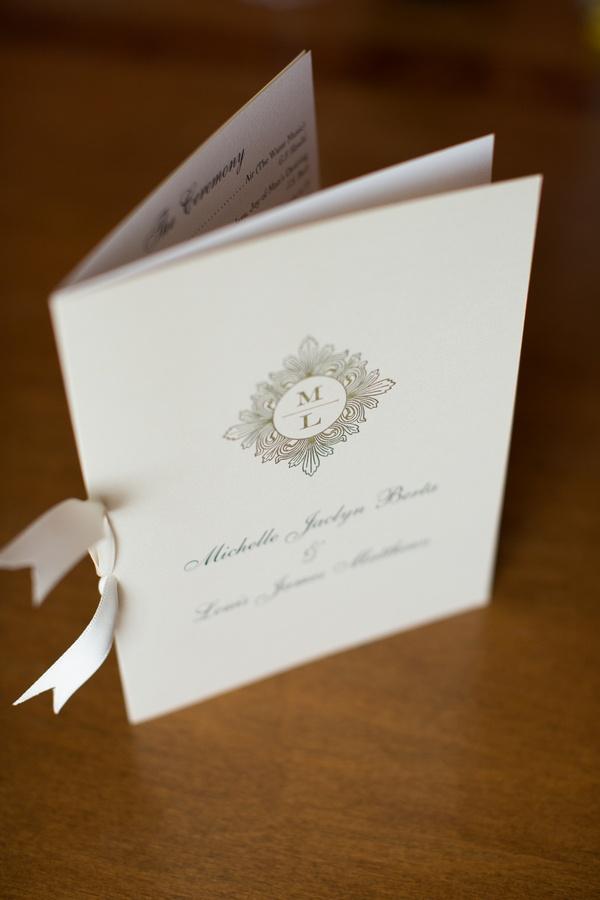 White bow tied to wedding program with monogram
