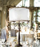 Iron candelabra centerpiece with white lamp shade and branches
