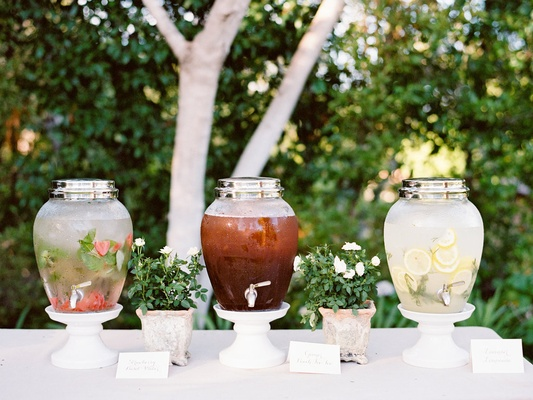 Outdoor wedding drink station with water, lemonade, and iced tea
