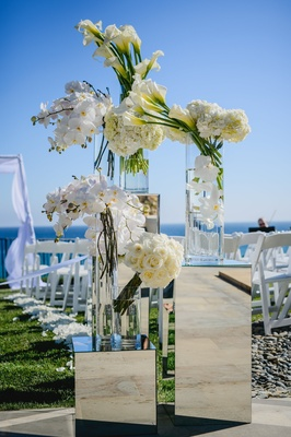 White calla lilies, orchids, hydrangea, and roses decorated the aisle.