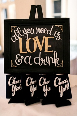 All you need is love & a drink sign, Cheers, Y'all! black koozies at wedding reception
