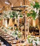 Wedding reception long table leather details bronze dark wood chandeliers greenery white flowers