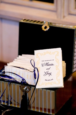 Wedding ceremony program tied with blue ribbon yellow design in mirror box