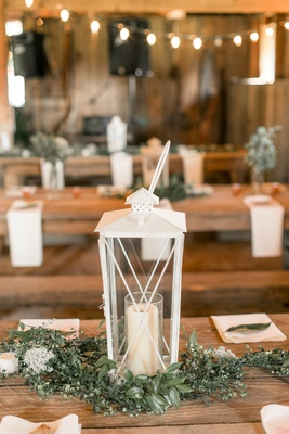 Wedding reception wood table white lantern greenery napkins leaf candle wood table