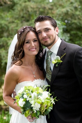 Bride in a Claire Pettibone gown and groom in a pinstripe suit and light green tie