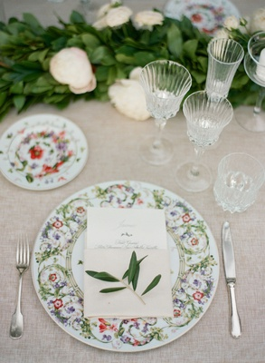 Wedding reception beige linen silver flatware crystal glassware garland sprig of greenery