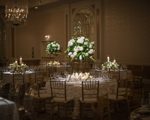 small round white tablescapes with tall floral arrangements featuring white flowers and foliage