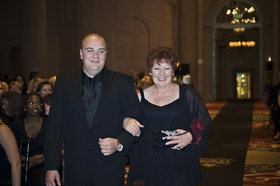 Lady in a black dress and wrap is escorted down the aisle by a man in a black tuxedo