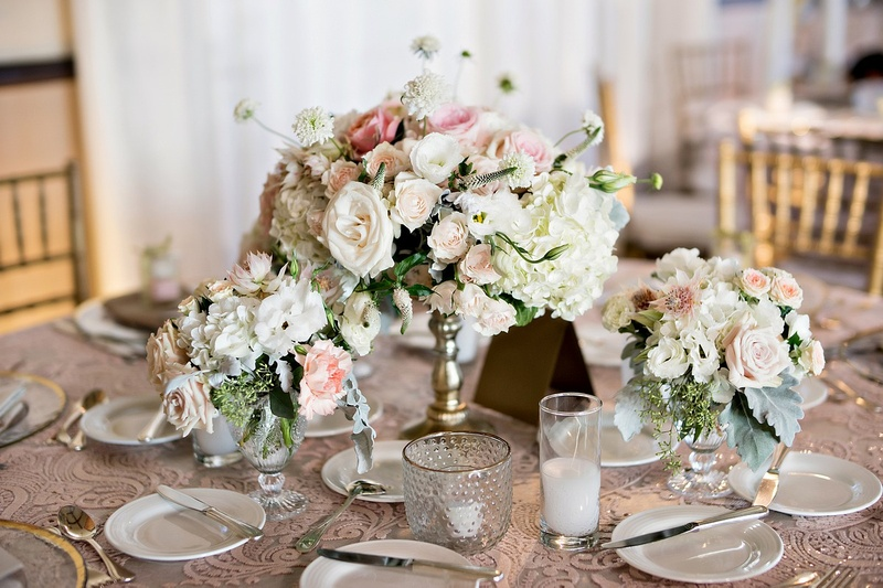 lower gold pedestal arrangement surrounded by candles,garden roses, hydrangea, exotic orchard blooms