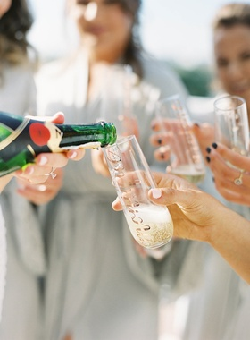 Moet and Chandon Champagne being poured for bridesmaids in robes personalized champagne flutes