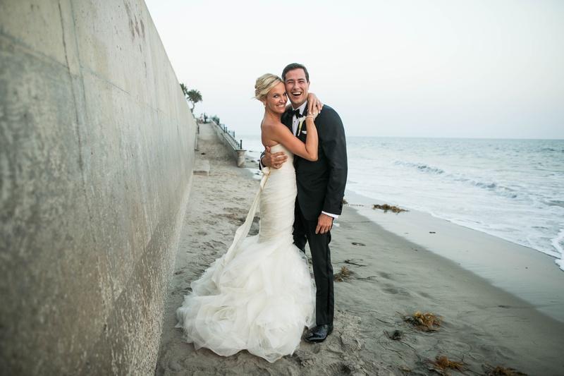 bride in gemma vera vang gown hugging groom in tux in front of wall on beach in santa barbara