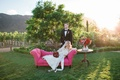 bride in jim hjelm wedding dress and groom relax on pink couch at california vineyard