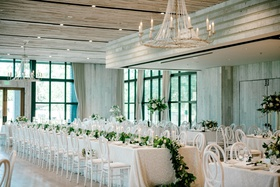 white wash wood room black frame windows white decor chairs linens greenery long garland chandelier