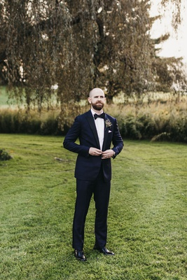 groom buttoning midnight blue tuxedo from bonobos while standing in a field