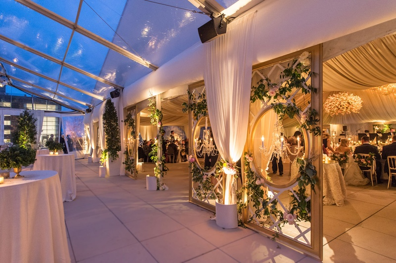Tent wedding view from cocktail hour space into reception ballroom drapery and open clear top tent