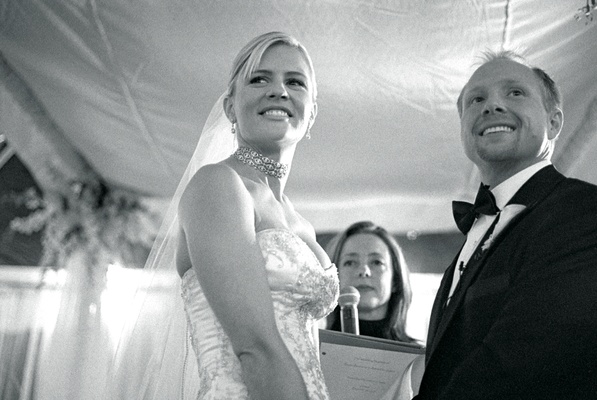 Black and white picture of couple at wedding ceremony altar