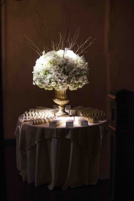 Wedding place card table with a large golden urn with white flowers