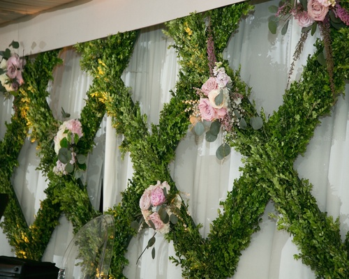 Criss cross boxwood frame accented by purple & blush bouquets.