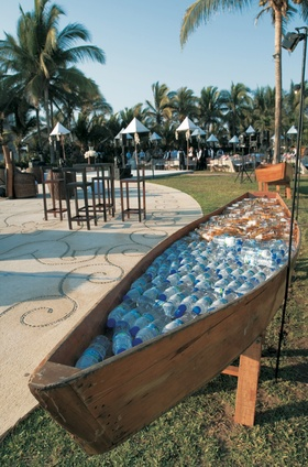 Bottled water and beer in wood boat at wedding reception