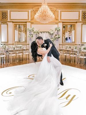 wedding reception ballroom white gold dance floor dip kiss husband and wife wedding