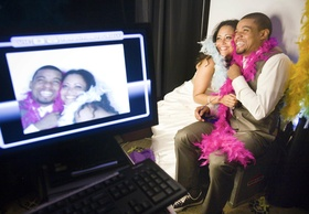 Bride and groom with pink and white feathers in front of photobooth