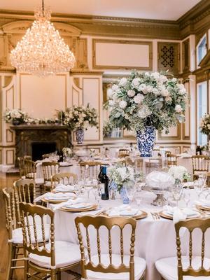 wedding reception historic ballroom blue white vase greenery white flowers gold chairs ornate