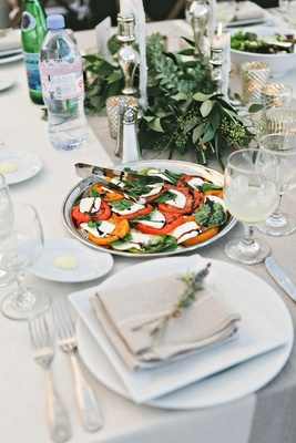 Farm wedding reception table with a silver platter of caprese salad, greenery garlands