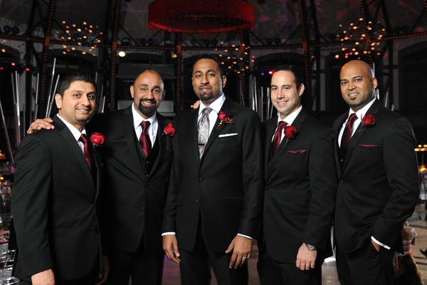 Indian man with friends in tuxedos at reception