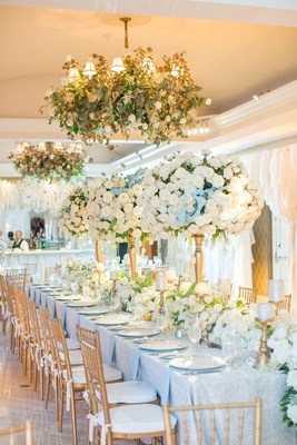 Head table with ivory flower runner, tall arrangements of roses, and chandeliers with greenery