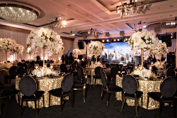 ballroom anniversary party gold linen black gold chairs white flower arrangements chandelier stage