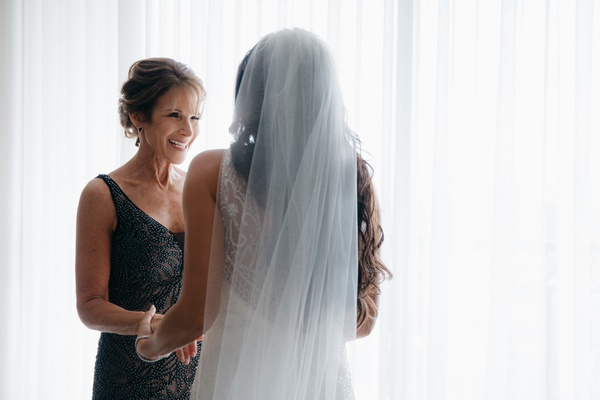 mother of the bride in sparkling embroidery black gown smiling at bride