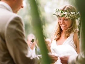 Bride at ceremony wearing white and green flower wreath