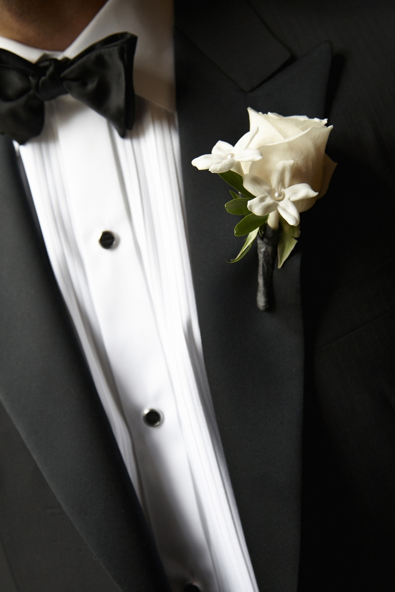 Groom wearing tuxedo fastened with rose and stephanotis