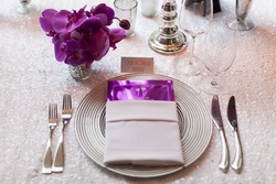 Metallic purple menu card in silver napkin on white sequin table