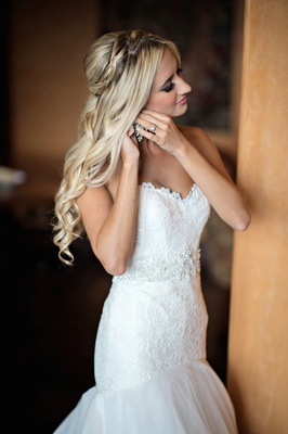Bride with blonde hair putting on earrings