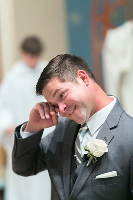 Happy groom in grey suit, grey & white striped tie, ivory rose boutonniere wipes tear at altar