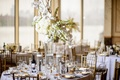 Tall glass centerpiece with hydrangeas, orchids, and branches with floating candles on either side