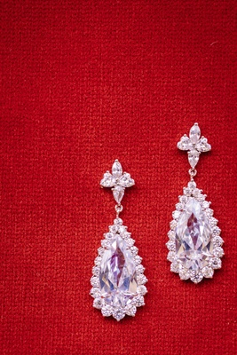 halo teardrop earrings, diamond earrings on red background