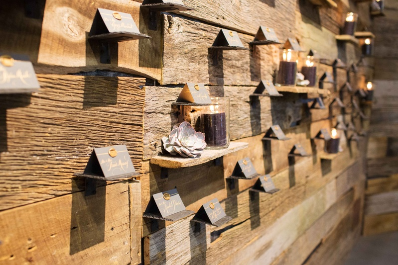Rustic wood wall with shelves, succulents, candles, escort cards with wax seals