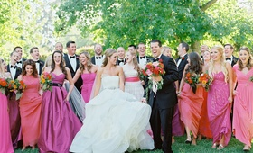 Bride in Vera Wang wedding dress with groom in tuxedo and bridesmaids in pink and orange dresses