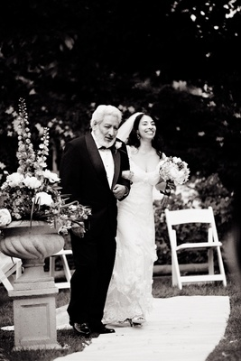 Black and white photo of bride in a Claire Pettibone gown walking down the aisle with her father