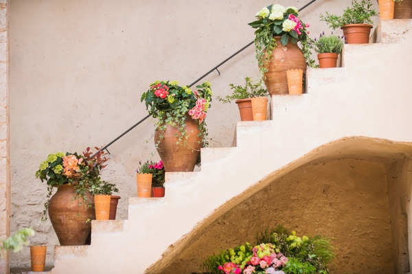 wedding reception abbey courtyard stone stairs terracotta planter vase pink flowers greenery lantern