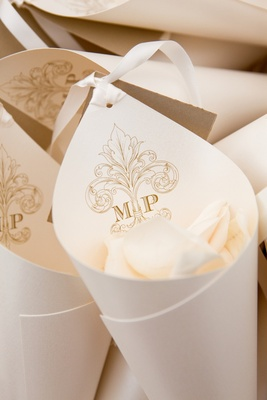 White rose petals in paper cone with wedding monogram