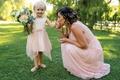 toddler falower girl with blush skirt holding bouquet, bridesmaid kisses flower girl's hand