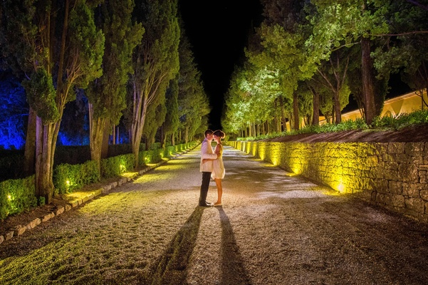 Bride in a Lanvin dress and groom in a white tuxedo jacket hug in a Tuscan night