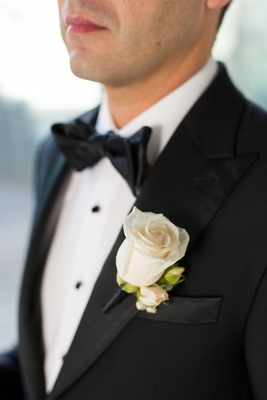 groom in black tuxedo, classic boutonniere cream rose with buds